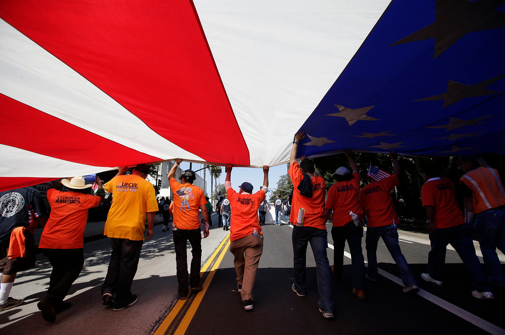 . Union workers march along the street with a huge American flag during a May Day rally in Los Angeles, Wednesday, May 1, 2013. In celebration of May Day, people have gathered across the country to rally for various topics including immigration reform. (AP Photo/Jae C. Hong)
