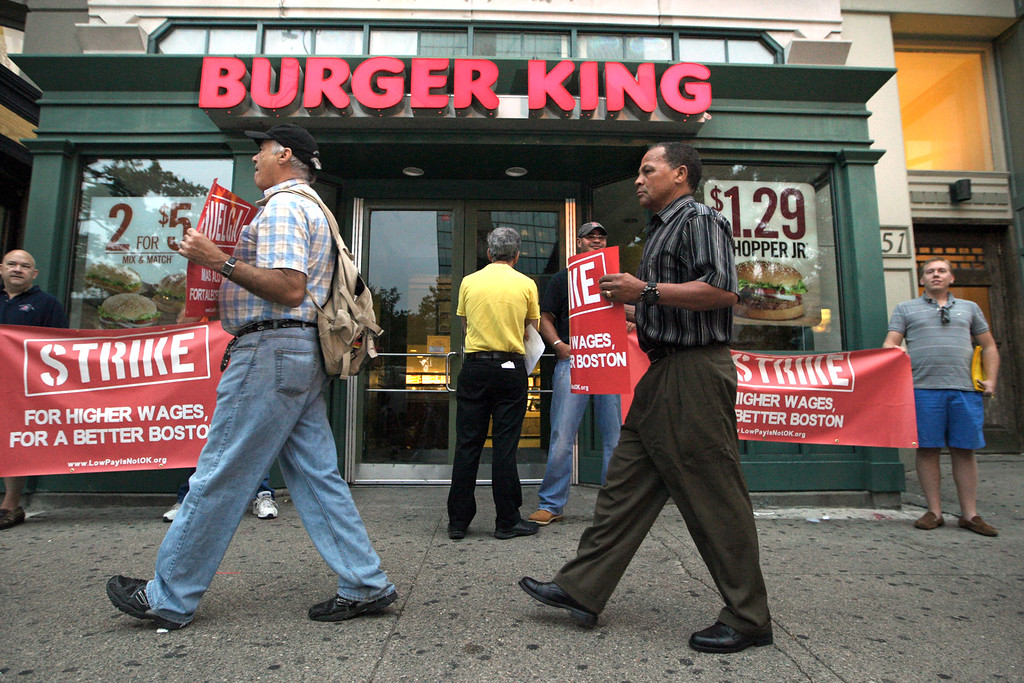 . Protesters display placards outside a Burger King fast food restaurant in Boston, Thursday, Aug. 29, 2013. The protest was one of several planned in Boston Thursday in what organizers say are similar walkouts planned in dozens of cities to push chains such as McDonald\'s, Taco Bell and Wendy\'s to pay workers more. (AP Photo/Boston Herald, Mark Garfinkel)