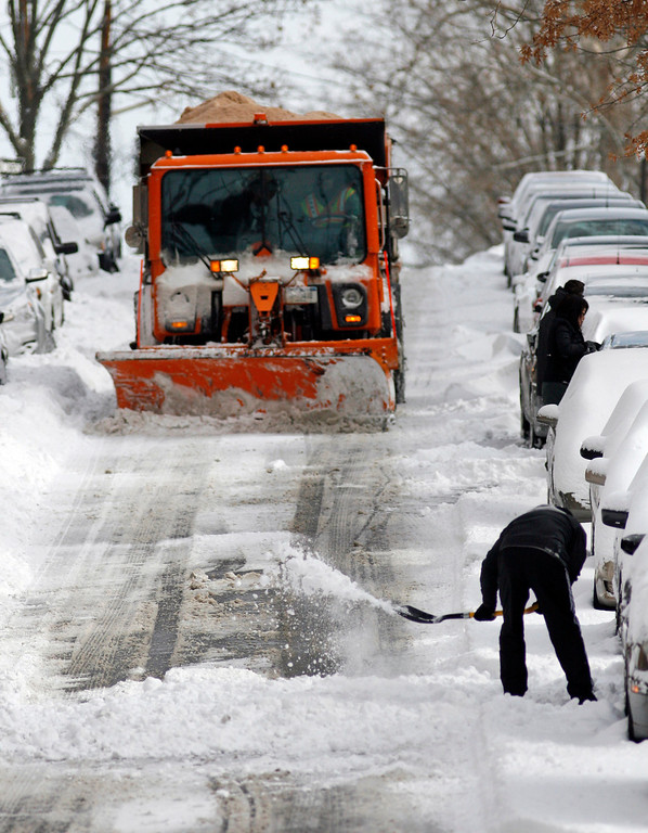 . In this Jan. 3, 2014 file photo, residents dig out their cars as a snow plow clears the street in the Queens borough of New York after an overnight snowstorm blew through the region. The major storm arrived in New York less than three days into Mayor Bill de Blasioís tenure. Critics and supporters alike will likely view the new Mayor\'s handling of the storm as the first test of his leadership.  (AP Photo/Daniel P. Derella, File)