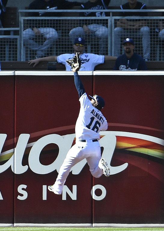. SAN DIEGO, CA - AUGUST 13:  Abraham Almonte #16 of the San Diego Padres makes a leaping catch at the wall to take away a hit from Drew Stubbs #13 of the Colorado Rockies during the first inning of a baseball game at Petco Park on August 13, 2014 in San Diego, California.  (Photo by Denis Poroy/Getty Images)