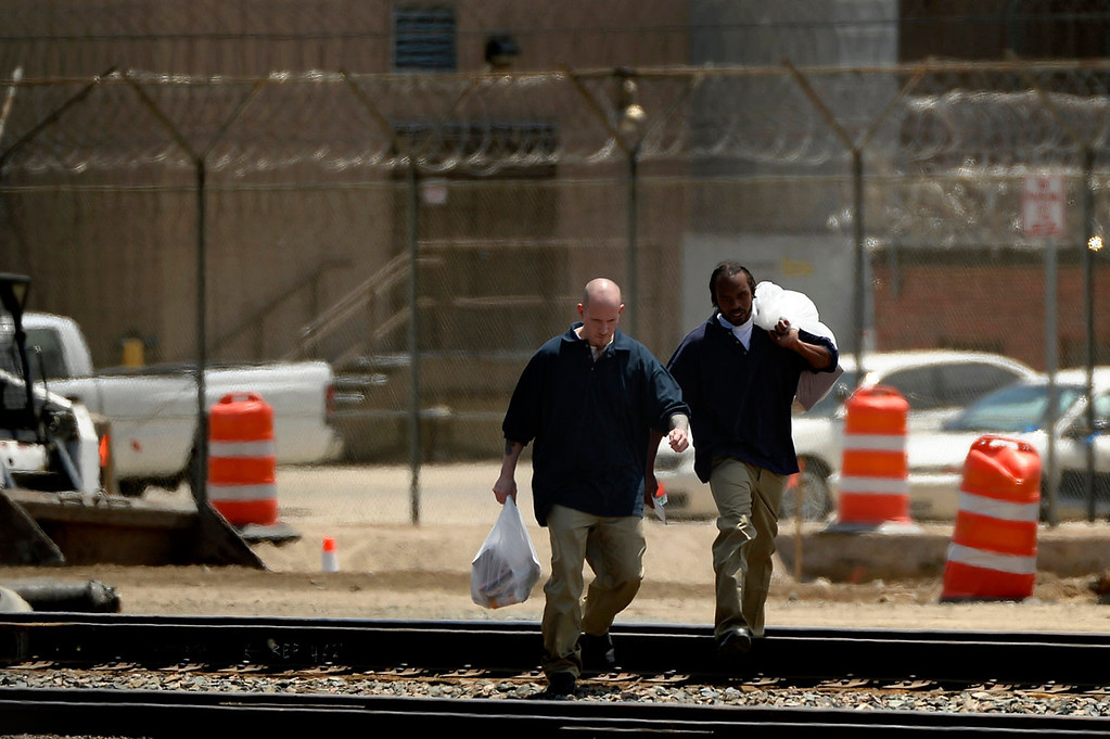 ". Parolee Thomas Vescio, 35, and Josh Hayward, 30, cross the railroad tracks at the Denver County Jail after being released from the Colorado Department of Corrections to start their parole on July 08, 2013 in Commerce City, Colorado. Vescio says he was ""state-raised,\"" in and out of foster care, juvenile detention and prison for 26 of his 35 years and this will be at least his 5th time on parole.  (Photo By Joe Amon/The Denver Post)"