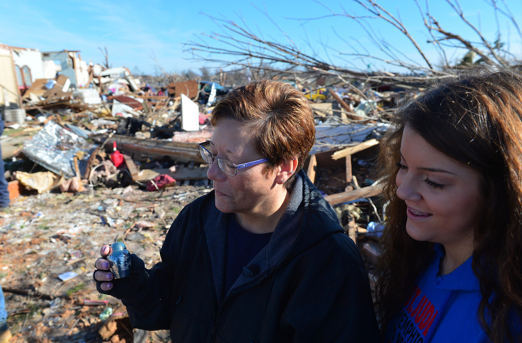 . Becky Holthe, along with her daughter Paige, right, is thankful to have found her father, or the urn containing his ashes in the rubble of their destroyed home in Washington. Ill., Tuesday, Nov. 19, 2013. Paige said that family photos, including her grandfathers obituary was found near Midway Airport. Homeowners dug out what they could Tuesday after more than 1,000 homes were devastated  by a F4 tornado that passed through Sunday. The twister was the most powerful to hit Illinois since 1885 with wind speeds greater than 200 mph. (AP Photo/Journal Star, Fred Zwicky)