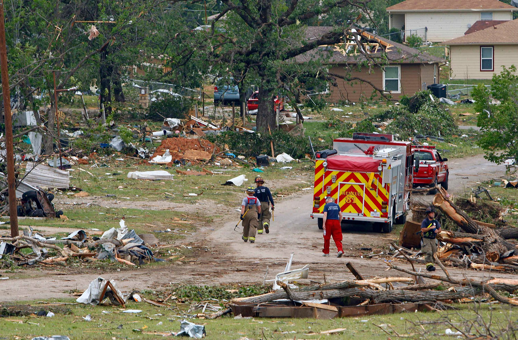 . Firefighters walk past debris May 16 after tornados swept through the town of Granbury, Texas late May 15, 2013.  REUTERS/Richard Rodriguez