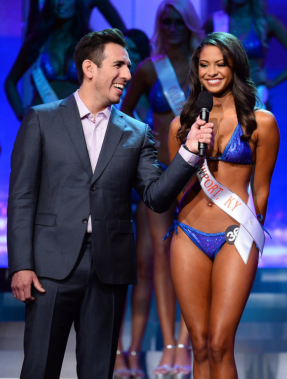 . Co-host and former mixed martial artist Kenny Florian (L) holds a microphone as Marissa Raisor of Newport, Kentucky answers a question during the interview portion of the 17th annual Hooters International Swimsuit Pageant at The Joint inside the Hard Rock Hotel & Casino on June 27, 2013 in Las Vegas, Nevada. Raisor went on to be crowned Miss Hooters International 2013.  (Photo by Ethan Miller/Getty Images)