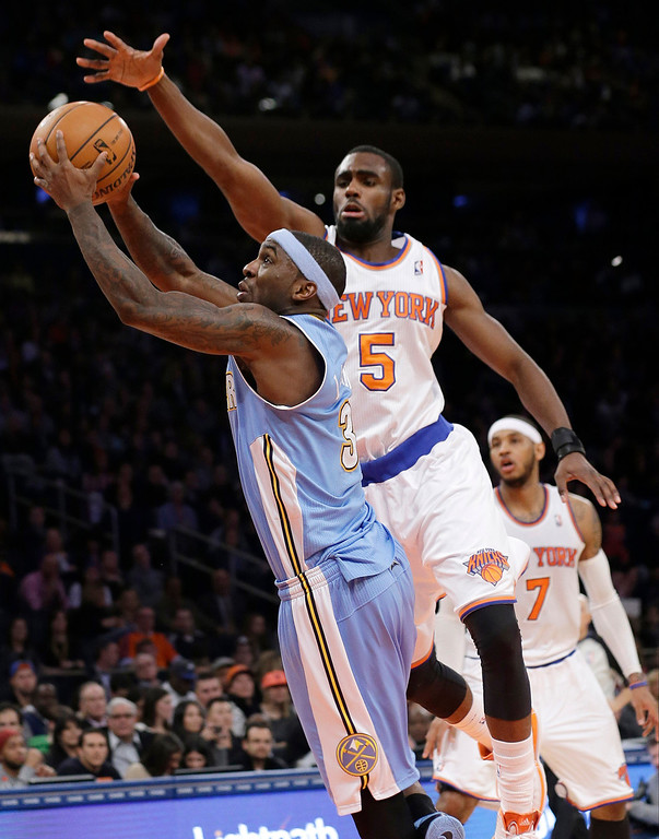 . Denver Nuggets\' Ty Lawson (3) drives past New York Knicks\' Tim Hardaway Jr. (5) during the second half of an NBA basketball game Friday, Feb. 7, 2014, in New York. The Knicks won the game 117-90. (AP Photo/Frank Franklin II)