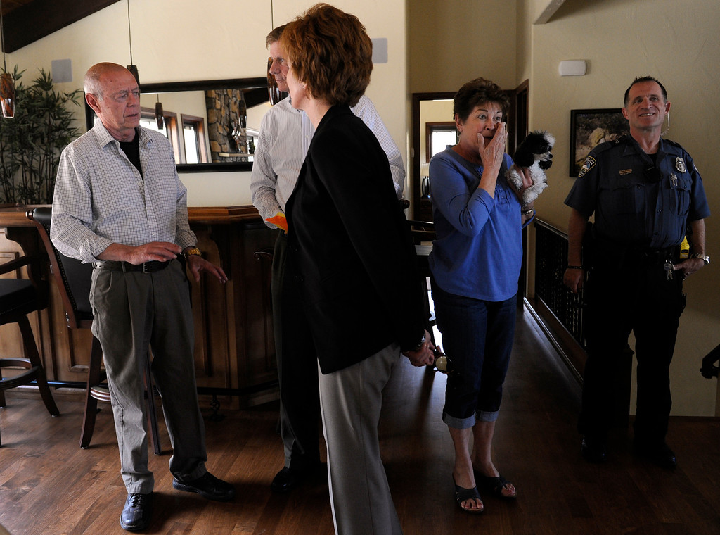 . Cynthia Flanagan, second from right, and her husband Bill, left, invite the mayor and his wife and officer Jimmy Paladino in to see their newly built home. The couple were able to move in to the house in early April. (Photo By Kathryn Scott Osler/The Denver Post)