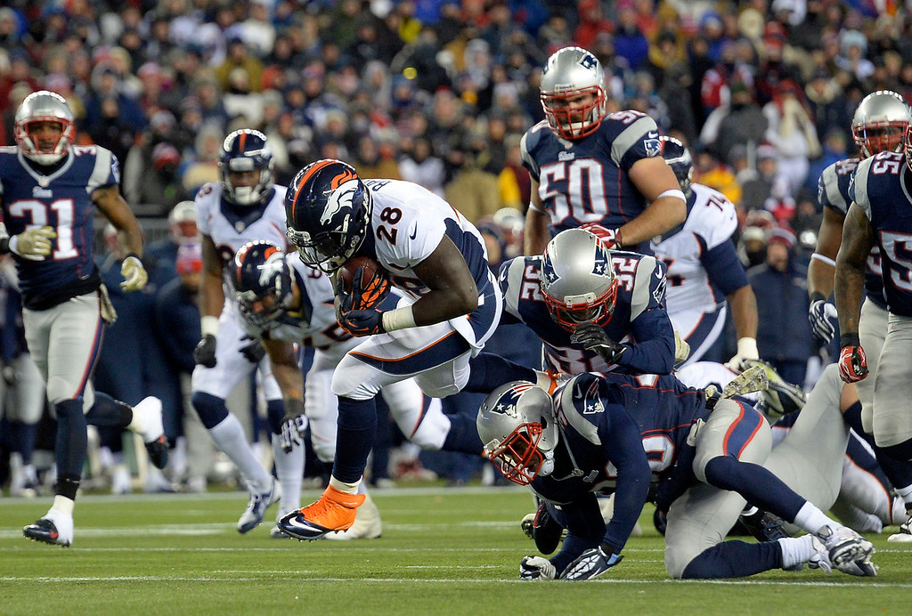 . Denver Broncos running back Montee Ball (28) runs over New England Patriots strong safety Duron Harmon (30) and New England Patriots free safety Devin McCourty (32) during the first quarter after a gain up the middle November 24, 2013 at Gillette Stadium. (Photo by John Leyba/The Denver Post)