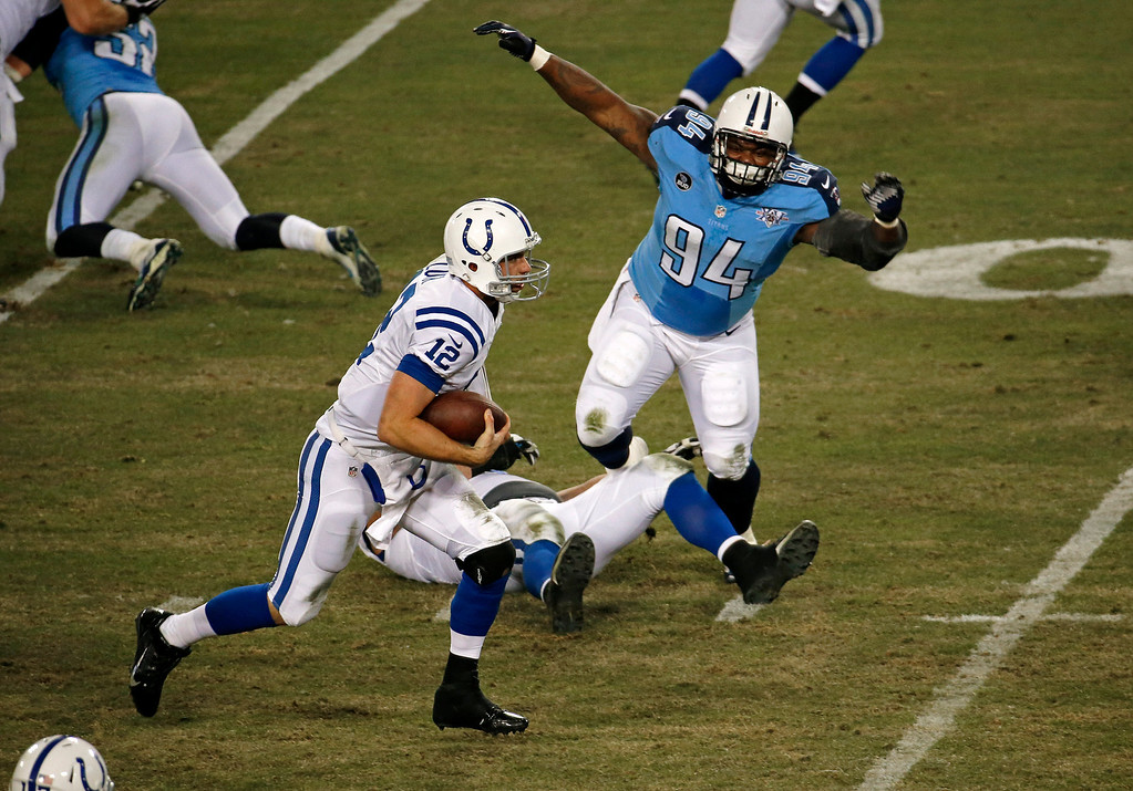 . Indianapolis Colts quarterback Andrew Luck (12) gets past Tennessee Titans defensive tackle Sammie Hill (94) as Luck runs 11 yards for a touchdown in the third quarter of an NFL football game Thursday, Nov. 14, 2013, in Nashville, Tenn. (AP Photo/Mark Zaleski)