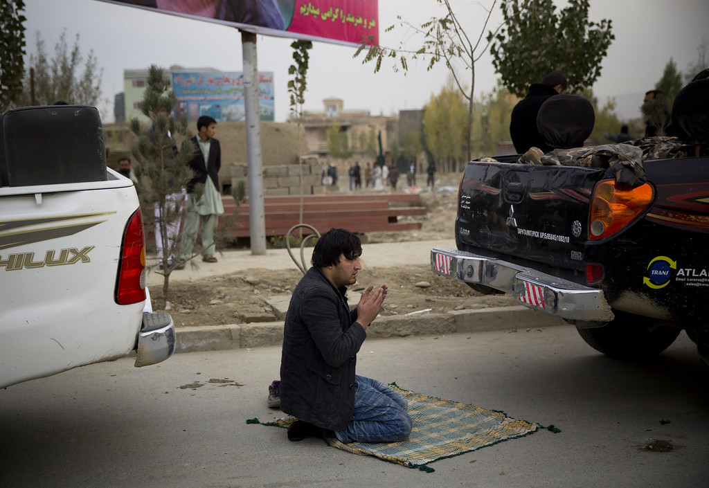 . An Afghan man prays between two police cars near the scene of a powerful suicide vehicle bomb on the outskirts of Kabul, Afghanistan, Saturday, Nov. 16, 2013.  (AP Photo/Anja Niedringhaus)