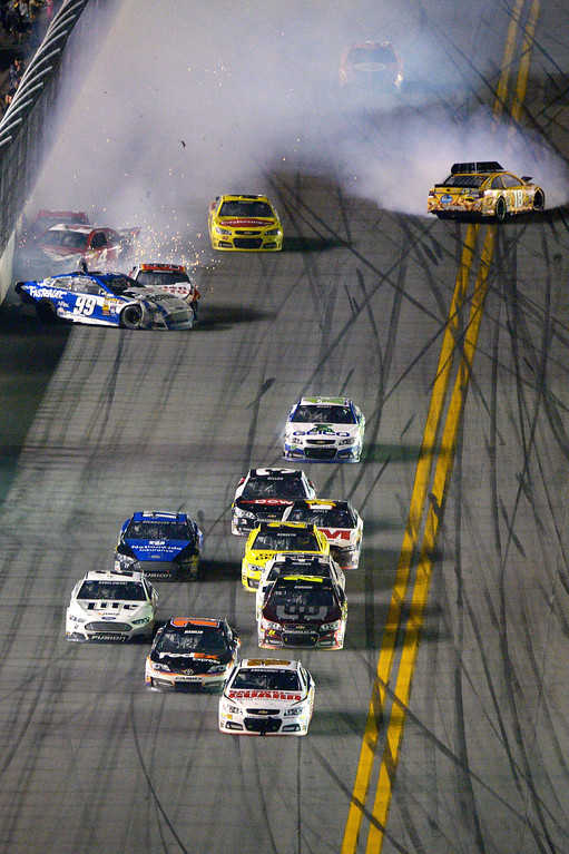 . Dale Earnhardt Jr. (88) escapes a final lap wreck and leads to the checkered flag to  win the NASCAR Daytona 500 auto race at Daytona International Speedway in Daytona Beach, Fla., Sunday, Feb. 23, 2014. (AP Photo/Phelan M. Ebenhack)
