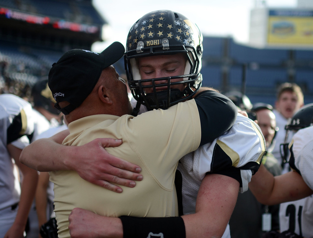 . Monarch QB Cole Watso, right, celebrate winning the 4A State Championship game against Denver South with a coach at Sports Authority Field at Mile High on Saturday, Dec. 1, 2012. Monarch won 17-14. Hyoung Chang, The Denver Post
