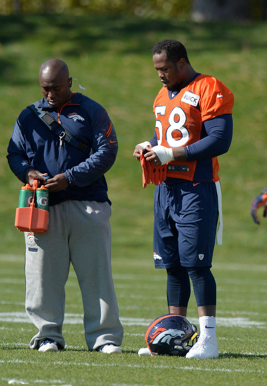 . Denver Broncos outside linebacker Von Miller (58) puts on his gloves during his first day back to practice October 16, 2013 at Dove Valley. Miller just finished serving a six game suspension. (Photo by John Leyba/The Denver Post)