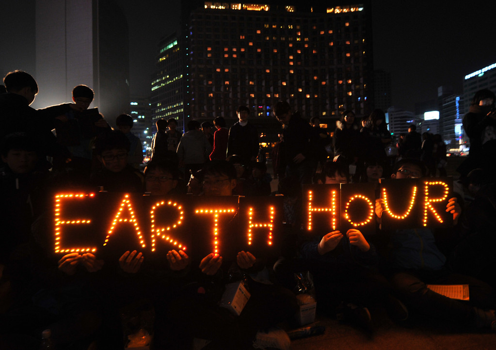 ". South Korean students hold an Earth Hour LED display during the 7th annual Earth Hour global warming campaign in Seoul on March 23, 2013. One minute brightly lit, the next plunged into darkness -- iconic landmarks around the world will cut their lights on March 23 for the ""Earth Hour\"" campaign against climate change.  JAE-HWAN/AFP/Getty Images"