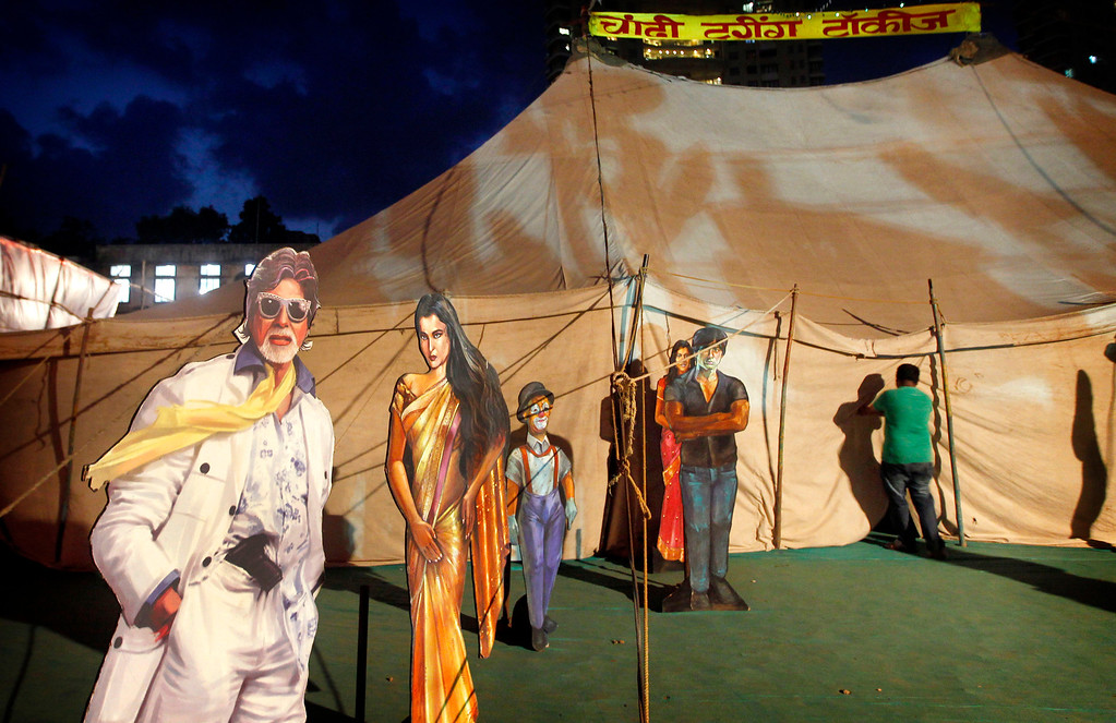 ". In this April 20, 2013 photo, cut outs of Indian Bollywood stars are displayed on the premises of the Anup Touring Talkies tent cinema in Mumbai, India. Friday, May 3 marks exactly a hundred years after India\'s first feature film ""Raja Harischandra,\"" a silent movie, was screened in 1913. India produced almost 1,500 movies last year and the industry is expected to grow from $ 2 billion to $ 3.6 billion in the next five years, according to consultancy KPMG. (AP Photo/Rajanish Kakade)"