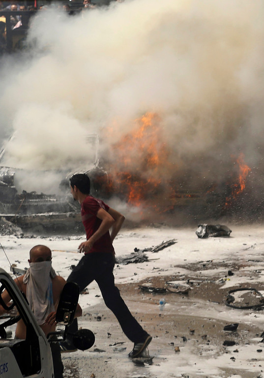 . Men run past burning cars at the site of an explosion in Beirut\'s southern suburbs, July 9, 2013. REUTERS/Issam Kobeisi