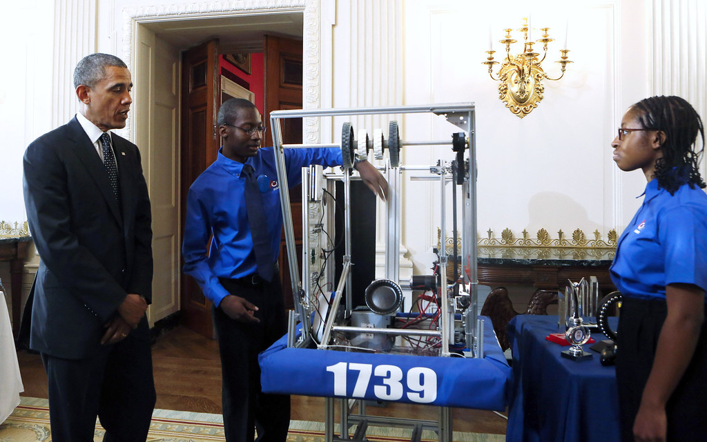 . U.S. President Barack Obama (L) looks at the First Robot  project of John Moore (C) and Lydia Wolfe of Chicago, Illinois, during the  2014 White House Science Fair at the White House, May 27, 2014 in Washington, DC. (Photo by Aude Guerruccip-Pool/Getty Images)