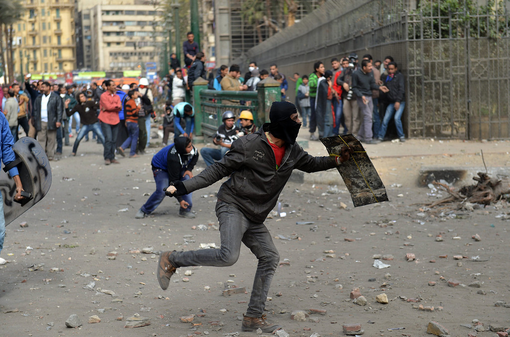 . Egyptian protestors take cover as others throw stones towards security personnel in Sheikh Rayhan street that leads to the Interior Ministry headquarters, near Tahrir Square, on January 25, 2013. Thousands of Egyptians marched in Tahrir Square to demand change, two years after the uprising that ousted Hosni Mubarak and ushered in an Islamist government, as sporadic clashes erupted nearby.  KHALED DESOUKI/AFP/Getty Images