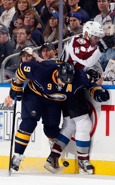 . Steve Ott #9 of the Buffalo Sabres checks Alex Tanguay #40 of the Colorado Avalanche at First Niagara Center on October 19, 2013 in Buffalo, New York.  (Photo by Jen Fuller/Getty Images)