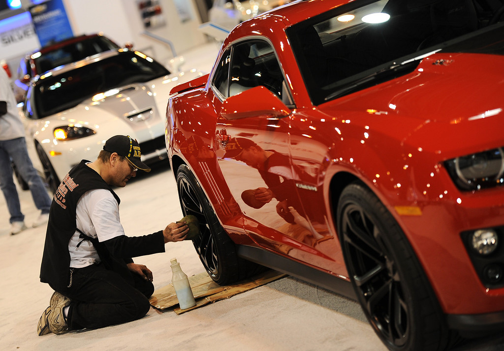 ". DENVER, CO- MARCH 19: James Whiteeagle of Professional Detailers cleans the tires of a 2013 Chevrolet Camaro on the showroom floor.  The Denver Auto Show is scheduled to opens Wednesday so preparation for the show is in full swing on March 19, 2013.  The show, which is at the Denver Convention Center, will run through the weekend.  The auto industry is putting renewed emphasis on natural gas-powered vehicles. The low prices of natural gas makes them an attractive option, especially for fleet operators. But a dearth of fueling stations. Also of interest at the show is the new prevalence of luxury cars such as Mercedes offering  ""affordable luxury\' models such as the Mercedes-Benz CLA, starting at $29,900. (Photo By Helen H. Richardson/ The Denver Post)"