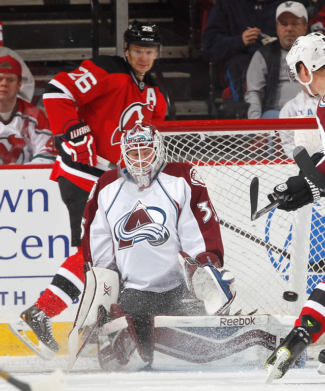 . Patrik Elias #26 of the New Jersey Devils watches as goalie Jean-Sebastien Giguere #35 of the Colorado Avalanche makes a save during the third period in an NHL hockey game at Prudential Center on February 3, 2014 in Newark, New Jersey.  Colorado won 2-1 in overtime.  (Photo by Paul Bereswill/Getty Images)