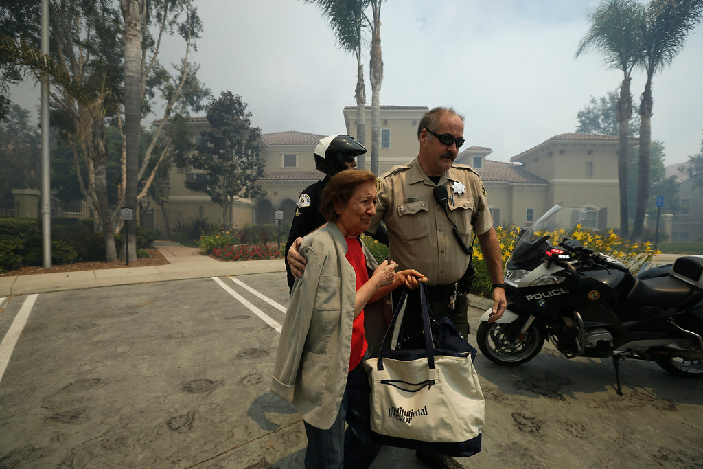 . A woman is evacuated from her building during a wildfire Wednesday, May 14, 2014, in Carlsbad, Calif. More wildfires broke out Wednesday in San Diego County  threatening homes in Carlsbad and forcing the evacuations of military housing and an elementary school at Camp Pendleton as Southern California is in the grip of a heat wave. (AP Photo)