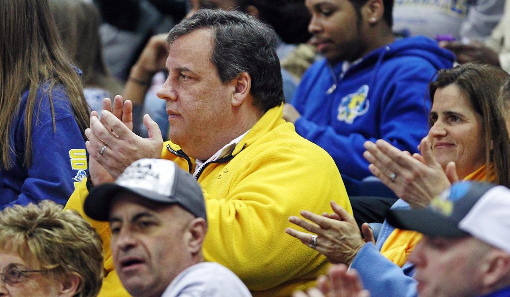 . New Jersey Gov. Chris Christie applauds during the first half of a regional semifinal between Delaware and Kentucky in the NCAA college basketball tournament in Bridgeport, Conn., Saturday, March 30, 2013. (AP Photo/Charles Krupa)
