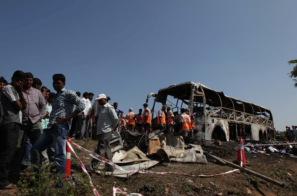 . Rescuers and others stand near the debris after a bus crashed into a highway barrier and erupted in flames at Mehabubnagar in southern Andhra Pradesh state, India, Wednesday, Oct. 30, 2013.  (AP Photo/Mahesh Kumar A.)