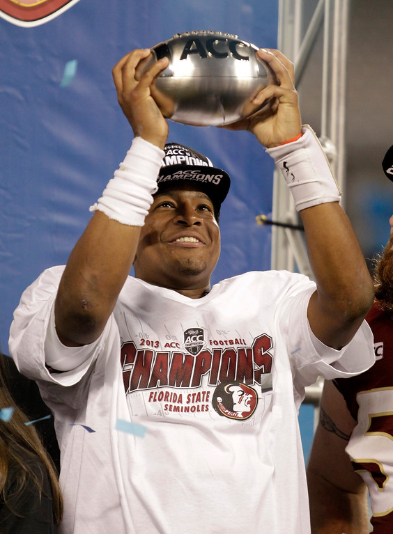 . Florida State\'s Jameis Winston holds up the trophy after the Atlantic Coast Conference Championship NCAA football game in Charlotte, N.C., Saturday, Dec. 7, 2013. Florida State defeated Duke 45-7. (AP Photo/Bob Leverone)