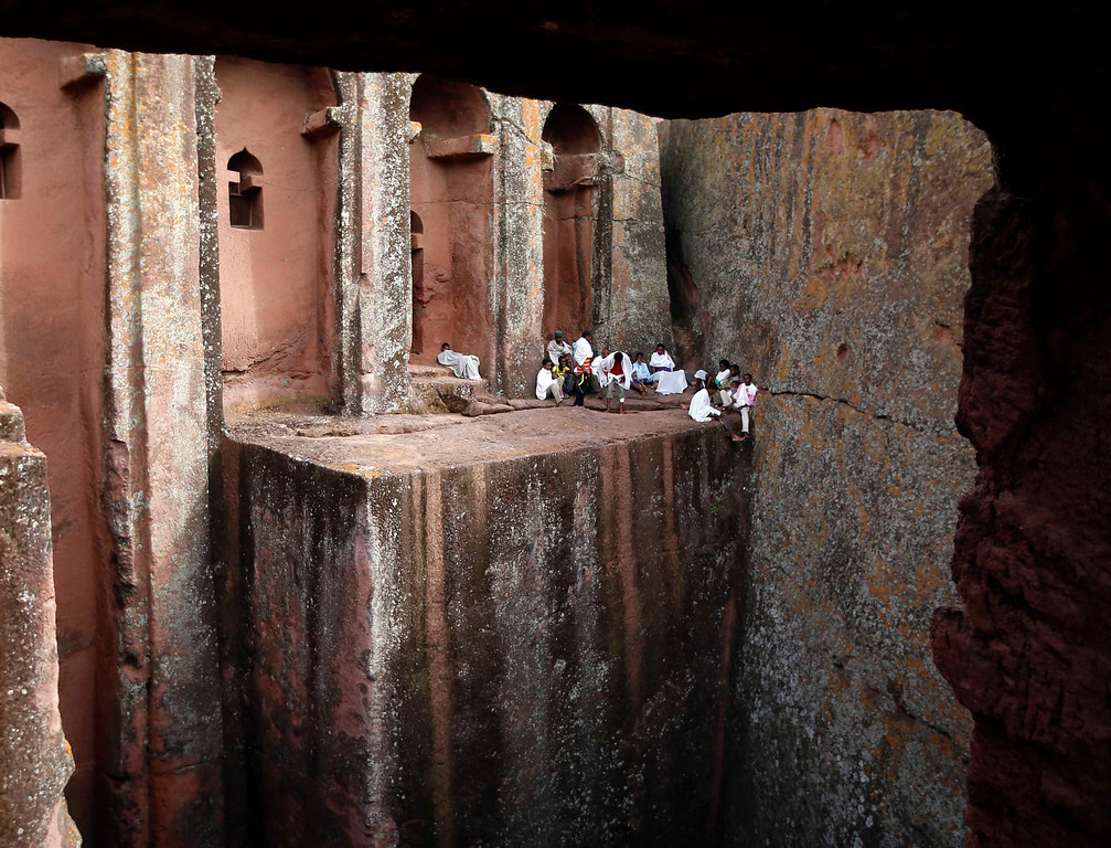 . Orthodox Christians sit outside the famous monolithic rock-cut churches during a Good Friday celebration in Lalibela May 3, 2013.  REUTERS/ Goran Tomasevic