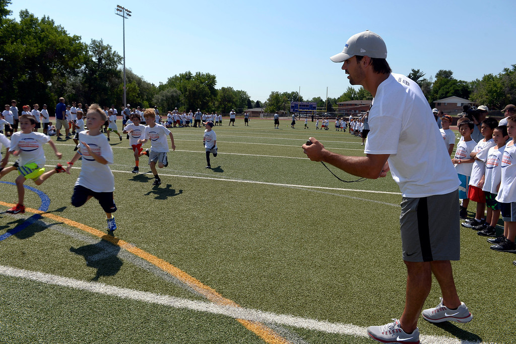 . Eric Decker times the campers in a race during camp. Demaryius Thomas and Eric Decker team up with ProCamps for their football camp held at Littleton High School July 11, 2013.  (Photo By John Leyba/The Denver Post)