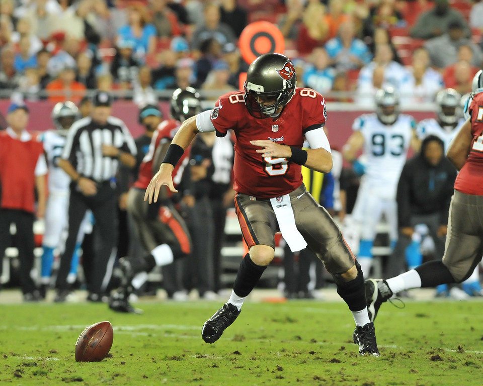 . TAMPA, FL - OCTOBER 24:  Quarterback Mike Glennon #8 of the Tampa Bay Buccaneers fumbles a snap in the 1st half against the Carolina Panthers October 24, 2013 at Raymond James Stadium in Tampa, Florida. (Photo by Al Messerschmidt/Getty Images)
