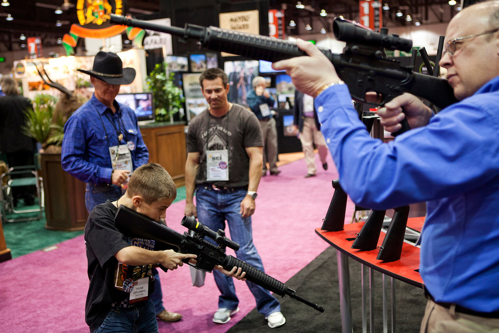 . Eleven-year-old Harrison Atwood (L) and Tony Miele (R) test Trijicon rifle scopes at the Safari Club International Convention in Reno, Nevada January 29, 2011. U.S. REUTERS/Max Whittaker