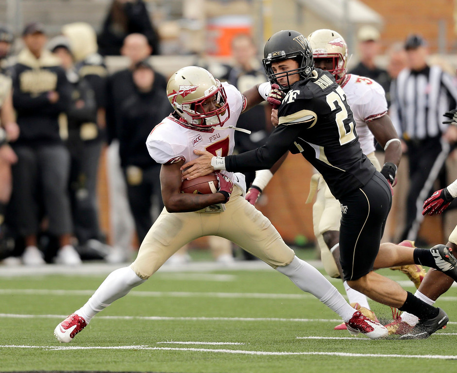 """. Florida State Levonte \""""Kermit\"""" Whitfield, ;eft, breaks away from Wake Forest kicker Chad Hedlund on the way to a touchdown in the second half of an NCAA college football game in Winston-Salem, N.C., Saturday, Nov. 9, 2013. (AP Photo/Nell Redmond)"""
