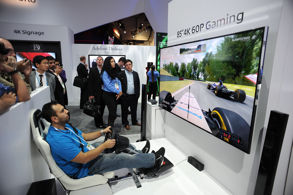 ". Attendee Kevin Shirzadian plays a ""Project Cars\"" on a 85\"" 4K 60P gaming display at the Panasonic booth  at the 2014 International CES in Las Vegas, Nevada, January 8, 2014.  The Consumer Electronics Show, one of the largest in the world, runs from Jan 7-10. AFP PHOTO / Robyn Beck/AFP/Getty Images"