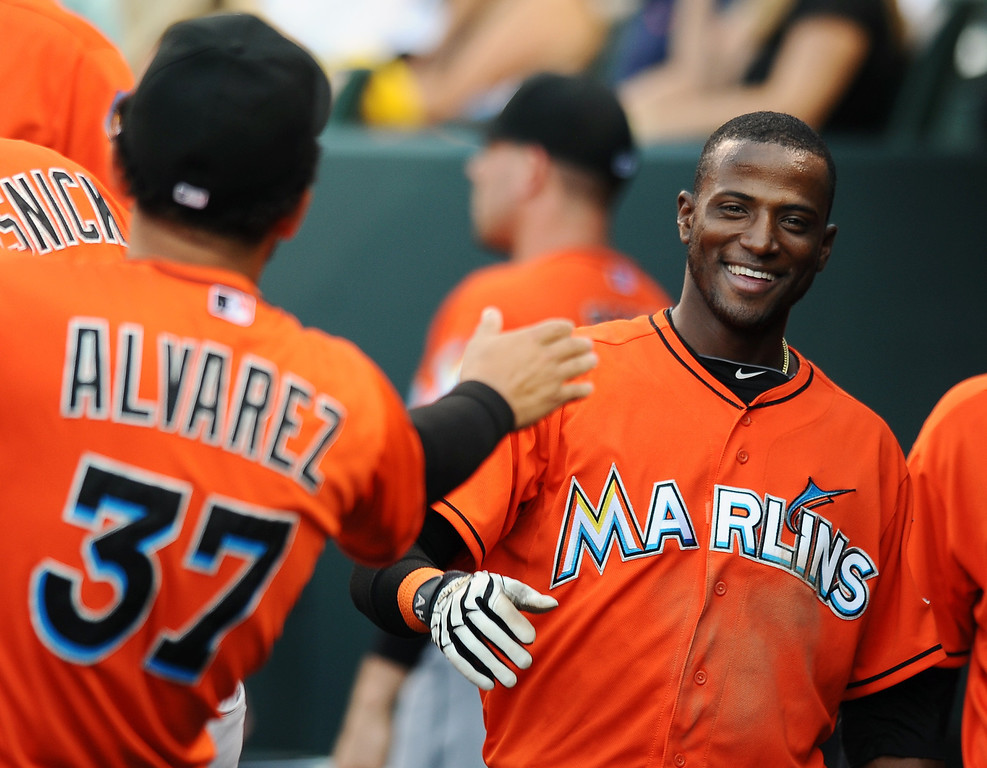 . Miami Marlins starting pitcher Henderson Alvarez, left, congratulates\' Adeiny Hechavarria after Hechavarria scored in the third inning of a baseball game against the Colorado Rockies on Tuesday, July 23, 2013 in Denver. (AP Photo/Chris Schneider)