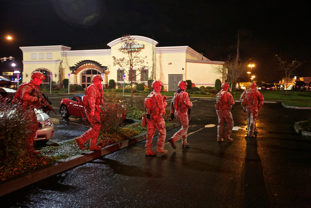 . A tactical team moves through the mall parking lot at Clackamas Town Center in Portland, Ore., Tuesday, Dec. 11, 2012. Witnesses say the scene went from cheery to chaotic in seconds when a gunman opened fire in the suburban Portland shopping mall Tuesday, killing two people and wounding another. (AP Photo/The Oregonian, Thomas Boyd)