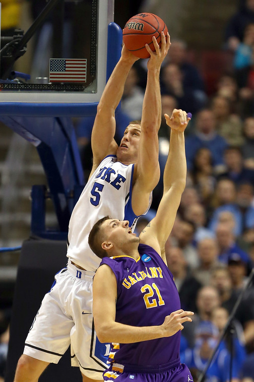 . Mason Plumlee #5 of the Duke Blue Devils catches a pass for a dunk over Blake Metcalf #21 of the Albany Great Danes in the first half during the second round of the 2013 NCAA Men\'s Basketball Tournament on March 22, 2013 at Wells Fargo Center in Philadelphia, Pennsylvania.  (Photo by Elsa/Getty Images)