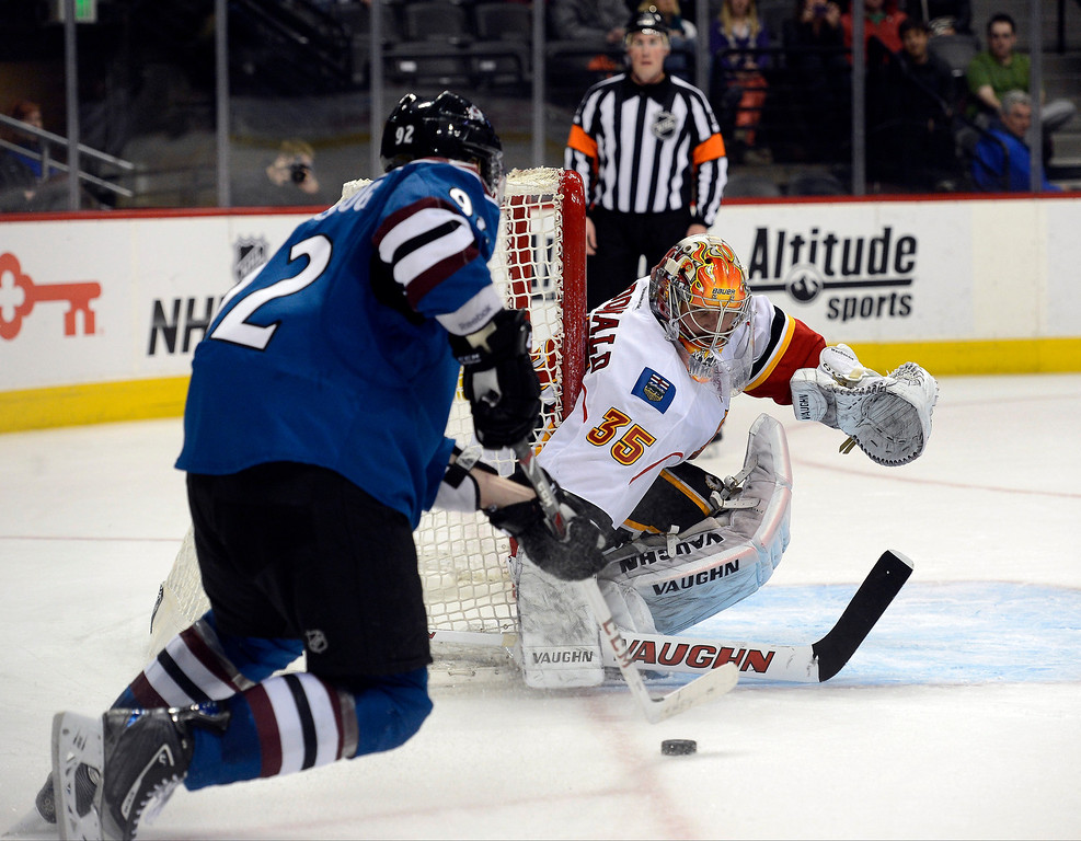 . Joey MacDonald (35) of the Calgary Flames reaches out with his stick as Gabriel Landeskog (92) of the Colorado Avalanche skates in with the puck during the third period April 8, 2013 at Pepsi Center. (Photo By John Leyba/The Denver Post)