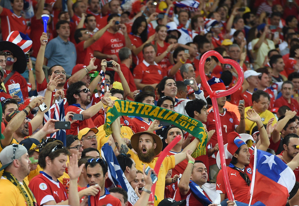 . Australia\'s and Chile\'s supporters cheer during a Group B football match between Chile and Australia at the Pantanal Arena in Cuiaba during the 2014 FIFA World Cup on June 13, 2014.     AFP PHOTO / WILLIAM WEST