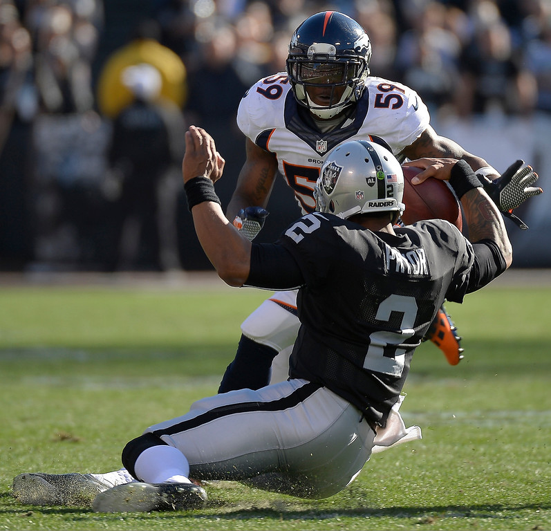 . Oakland Raiders quarterback Terrelle Pryor (2) slides for a few yards before he is hit by Denver Broncos outside linebacker Danny Trevathan (59) during the first quarter at O.co Coliseum. (Photo by John Leyba/The Denver Post)