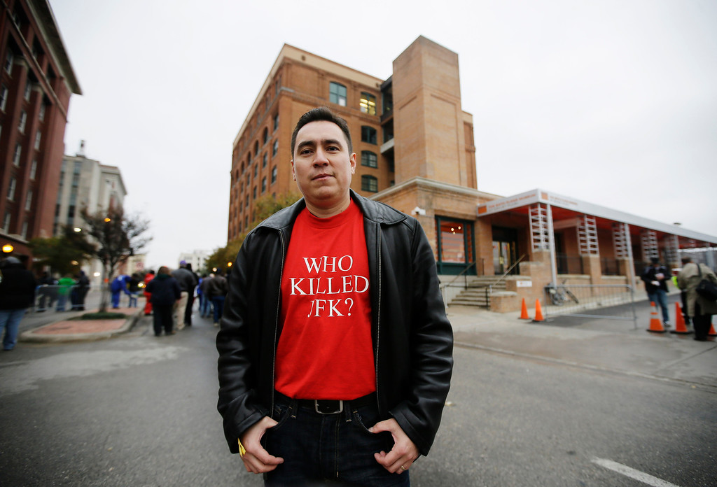 . Chato Prado, 39, from Chicago pauses for a photo in front of the Texas School book Depository building before a ceremony to mark the 50th anniversary of the assassination of John F. Kennedy, Friday, Nov. 22, 2013, at Dealey Plaza in Dallas. President Kennedy\'s motorcade was passing through Dealey Plaza when shots rang out on Nov. 22, 1963. (AP Photo/Tony Gutierrez)