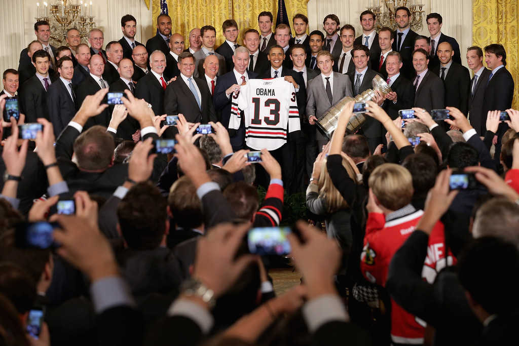 . Guests use mobile phone cameras to record U.S. President Barack Obama as he poses for photographs with the National Hockey League 2013 champion Chicago Blackhawks in the East Room of the White House November 4, 2013 in Washington, DC. This is the second visit to the White House in as many years for the Blackhawks, who won the Stanley Cup in 2010.  (Photo by Chip Somodevilla/Getty Images)