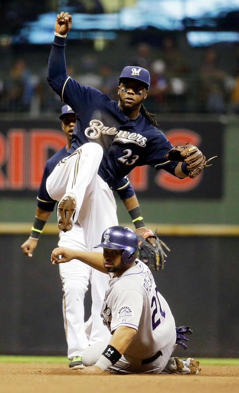 . Colorado Rockies\' Wilin Rosario (20) is out at second as Milwaukee Brewers\' Rickie Weeks turns a double play on a ball hit by Vinny Castilla during the sixth inning of a baseball game Thursday, June 26, 2014, in Milwaukee. (AP Photo/Morry Gash)