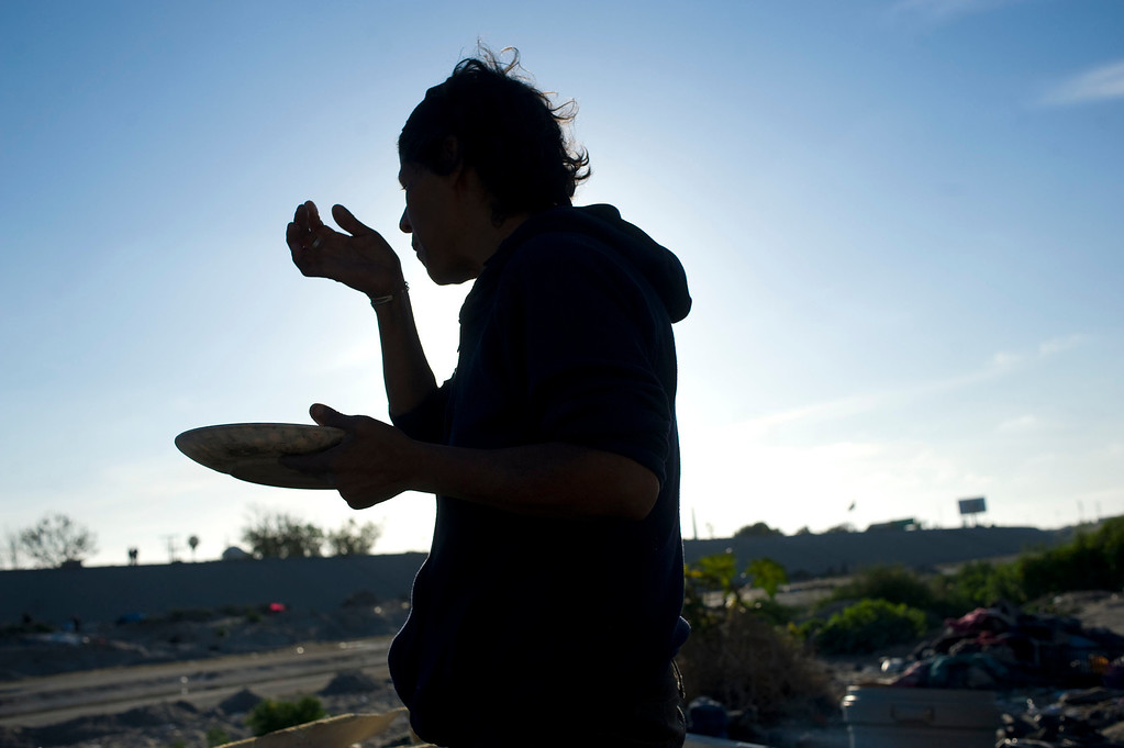 . Marta Gomez, 42, eats fish found in a nearby market in the Tijuana River canal, which has become home to hundreds of people deported from the US, in Tijuana, Mexico, 27 March 2013. Gomez was deported three years ago and has been living homeless in the canal. She has nine children who live in the United States. Heightened US border security and record numbers of deportations from the US have created a growing population of people who live homeless in Mexican cities that border with the United States. Many had lived for years undocumented in the US and have little or no family and other support in Mexico, and are subject to fall into depression, substance abuse and crime. Tijuana, Mexico, borders on the US city of San Diego, California.  EPA/DAVID MAUNG