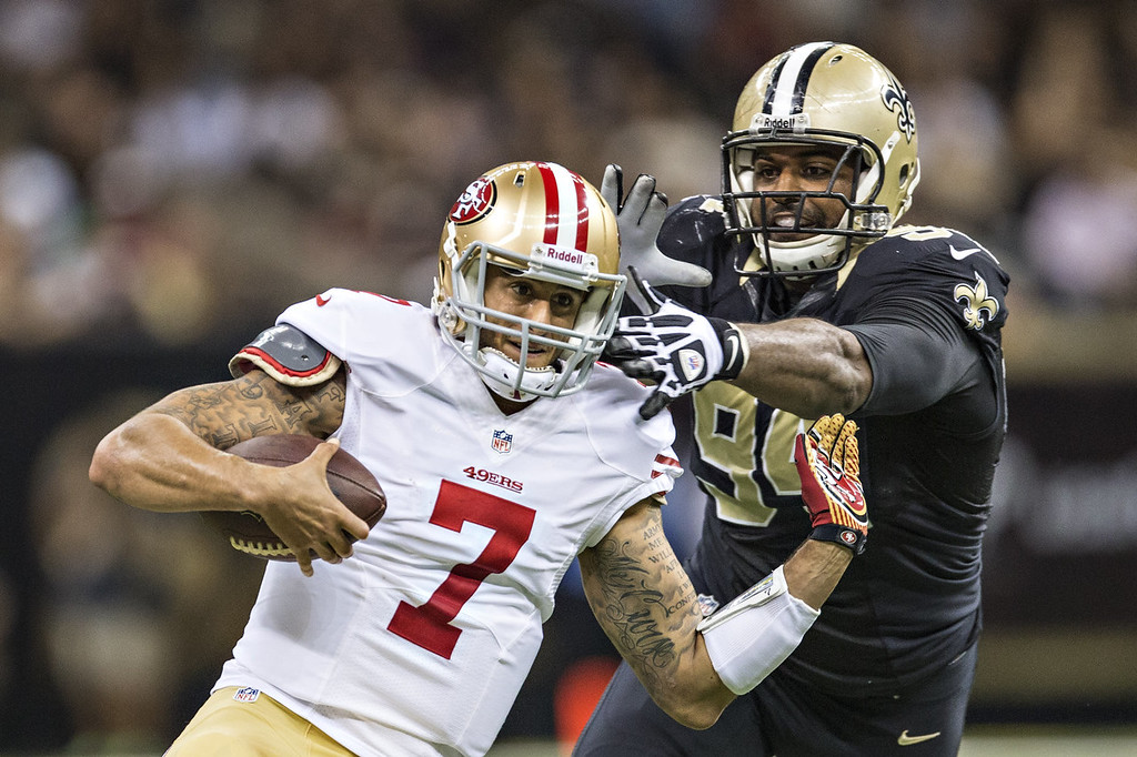 . Colin Kaepernick #7 of the San Francisco 49ers slides below the tackle Cameron Jordan #94 of the New Orleans Saints at  Mercedes-Benz Superdome on November 17, 2013 in New Orleans, Louisiana.  The Saints defeated the 49ers 23-20.  (Photo by Wesley Hitt/Getty Images)