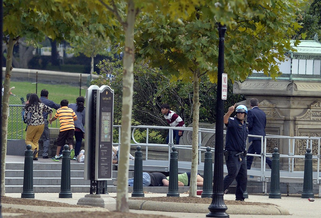 ". People take cover as gun shoot being heard at the Capitol in Washington, DC, on October 3, 2013. The US Capitol was placed on security lockdown Thursday after shots were fired outside the complex, senators said. ""Shots fired outside the Capitol. We are in temporary lock down,\"" Senator Claire McCaskill said on Twitter. Police were seen running within the Capitol building and outside as vehicles swarmed to the scene. AFP Photo/Jewel  SAMAD/AFP/Getty Images"