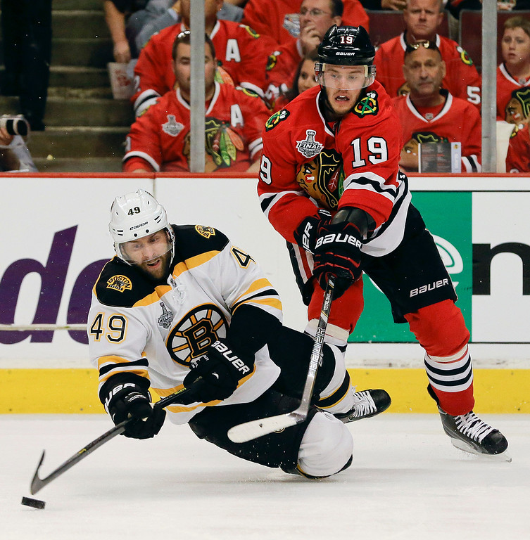 . Boston Bruins center Rich Peverley (49) falls to the ice as he keeps the puck from Chicago Blackhawks center Jonathan Toews (19) in the second period during Game 2 of the NHL hockey Stanley Cup Finals, Saturday, June 15, 2013, in Chicago. (AP Photo/Nam Y. Huh)