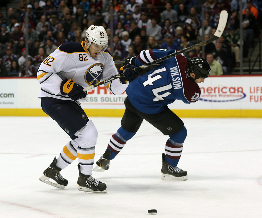 . Buffalo Sabres left wing Marcus Foligno, left, clears away Colorado Avalanche defenseman Ryan Wilson to take control of the puck in the first period of an NHL hockey game in Denver, Saturday, Feb. 1, 2014. (AP Photo/David Zalubowski)