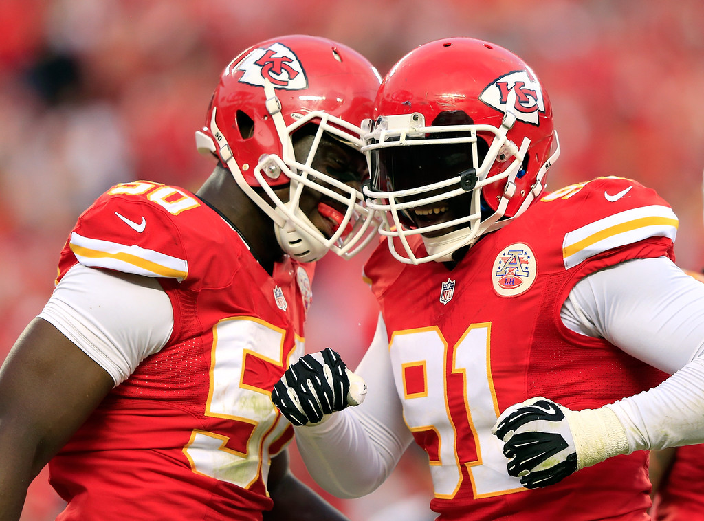 . Outside linebacker Tamba Hali #91 of the Kansas City Chiefs is congratulated by outside linebacker Justin Houston #50 after sacking quarterback Case Keenum #7 of the Houston Texans late in the 2nd half of the game at Arrowhead Stadium on October 20, 2013 in Kansas City, Missouri.  (Photo by Jamie Squire/Getty Images)