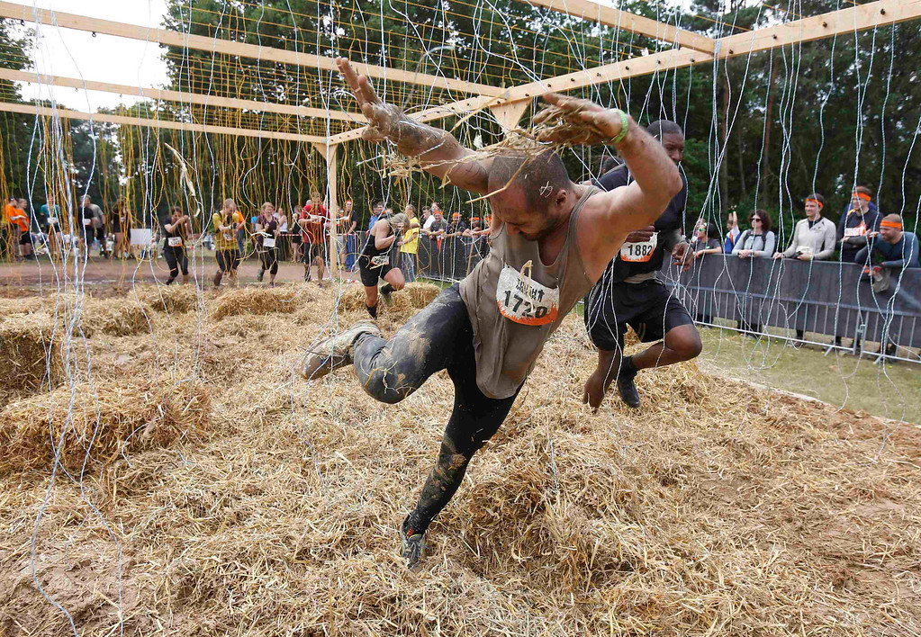 """. A participant of the \""""Tough Mudder\"""" endurance event series struggles in the \""""Electroshock Therapy\"""" obstacle made of electrical wire holding some 10,000 Volts in the Fursten Forest, a former British Army training ground near the north-western German city of Osnabrueck July 13, 2013. The hardcore but un-timed event over 16 km (10 miles) was designed by British Special Forces to test mental as well as physical strength. Some 4,000 competitors had to overcome obstacles of common human fears, such as fire, water, electricity and heights.   REUTERS/Wolfgang Rattay"""